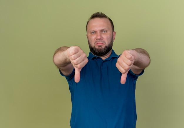 Niezadowolony dorosły słowiański mężczyzna pokazujący kciuki w dół