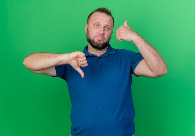 Niezadowolony dorosły słowiański mężczyzna pokazujący kciuki w górę iw dół na białym tle na zielonej ścianie