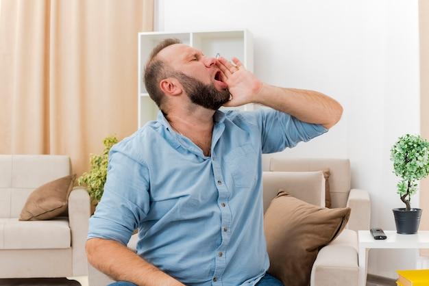 Niezadowolony dorosły słowiański mężczyzna siedzi na fotelu trzymając rękę blisko ust, patrząc w bok, udając, że dzwoni do kogoś w salonie