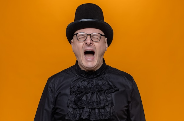 Niezadowolony dorosły słowiański mężczyzna w cylindrze i okularach optycznych w czarnej gotyckiej koszuli krzyczy stojąc z zamkniętymi oczami