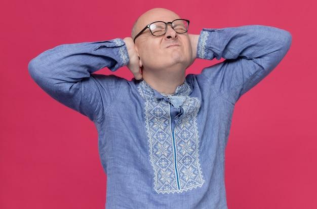 Niezadowolony dorosły słowiański mężczyzna w niebieskiej koszuli w okularach optycznych zamykający uszy rękami