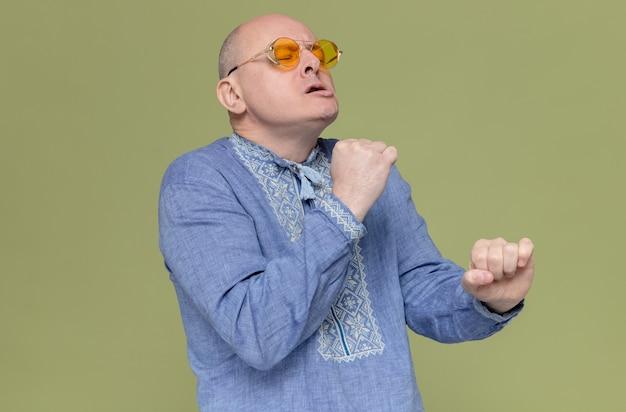Niezadowolony dorosły słowiański mężczyzna w niebieskiej koszuli w okularach przeciwsłonecznych stoi z zamkniętymi oczami i udaje, że coś trzyma