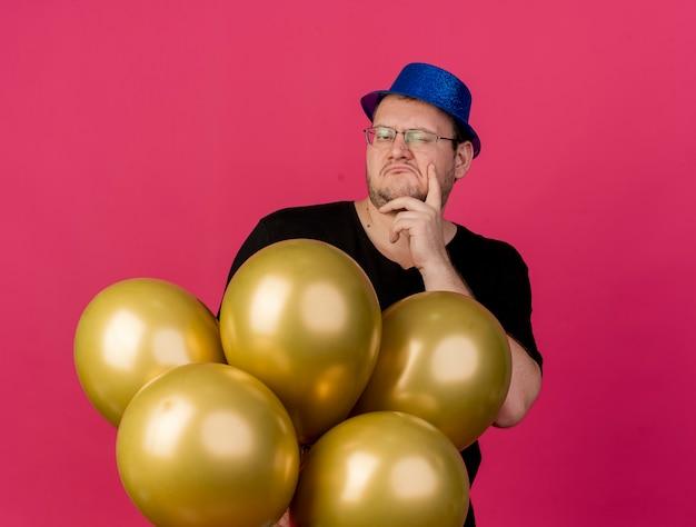 Niezadowolony dorosły słowiański mężczyzna w okularach optycznych w niebieskiej imprezowej czapce kładzie rękę na brodzie i trzyma balony z helem, patrząc w kamerę