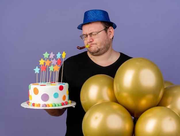 Niezadowolony dorosły słowiański mężczyzna w okularach optycznych w niebieskiej imprezowej czapce stoi z balonami z helem, trzymając tort urodzinowy i dmuchając w gwizdek