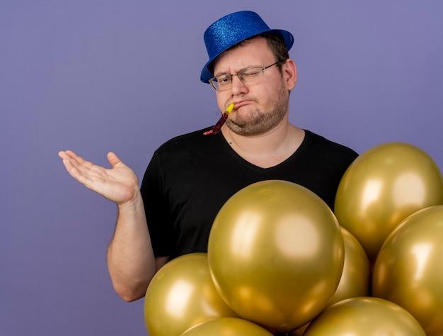 Niezadowolony dorosły słowiański mężczyzna w okularach optycznych w niebieskim kapeluszu imprezowym stoi z balonami z helem dmuchającym w gwizdek