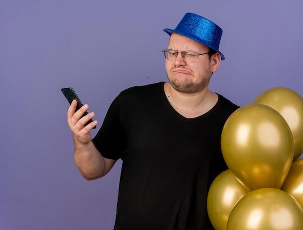 Niezadowolony dorosły słowiański mężczyzna w okularach optycznych w niebieskim kapeluszu imprezowym trzyma balony z helem i telefon