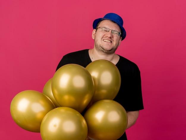 Niezadowolony dorosły słowiański mężczyzna w okularach optycznych w niebieskim kapeluszu imprezowym trzyma balony z helem