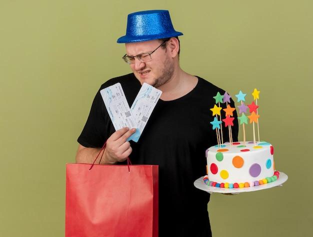 Niezadowolony dorosły słowiański mężczyzna w okularach optycznych w niebieskim kapeluszu imprezowym trzyma papierową torbę na zakupy tort urodzinowy i bilety lotnicze air