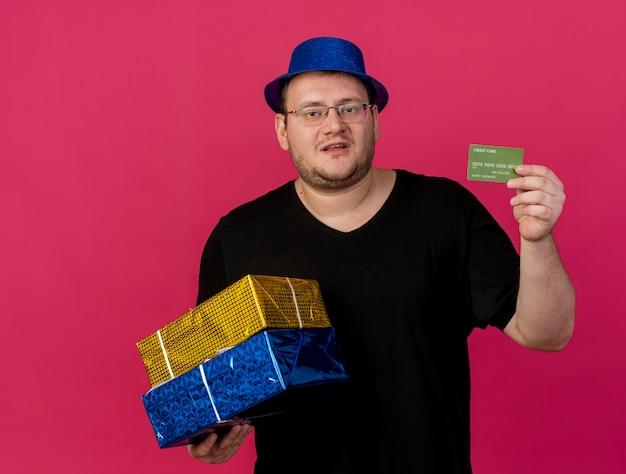 Niezadowolony dorosły słowiański mężczyzna w okularach optycznych w niebieskim kapeluszu imprezowym trzyma pudełka na prezenty i kartę kredytową