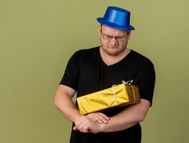 Niezadowolony dorosły słowiański mężczyzna w okularach optycznych w niebieskim kapeluszu imprezowym trzyma pudełko upominkowe