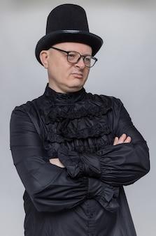 Niezadowolony dorosły słowiański mężczyzna z cylindrem i okularami optycznymi w czarnej gotyckiej koszuli stojący ze skrzyżowanymi rękami i patrzący na bok