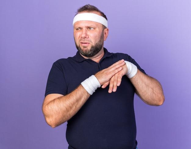 Niezadowolony dorosły słowiański sportowy mężczyzna noszący opaskę i opaski trzymające się za ręce i patrzący na bok odizolowany na fioletowej ścianie z kopią miejsca