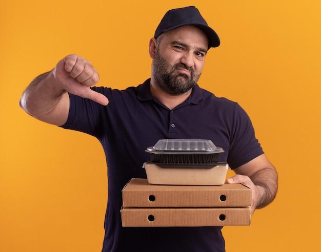 Niezadowolony dostawczyni w średnim wieku w mundurze i czapce trzymający pojemnik z jedzeniem na pudełkach po pizzy pokazujący kciuk w dół na żółtej ścianie