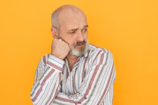 Niezadowolony emerytowany starszy mężczyzna z siwą brodą i łysiną pozowanie na białym tle pięścią na policzku