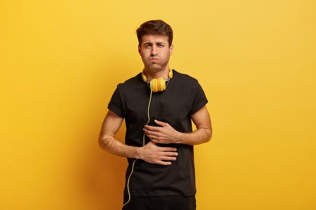 Niezadowolony facet cierpi na złe samopoczucie, dyskomfort w żołądku, wymioty
