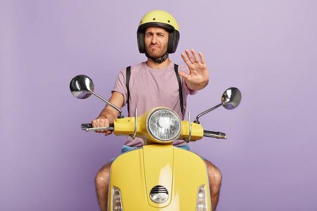 Niezadowolony facet w kasku prowadzący żółty skuter