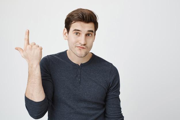 Niezadowolony facet wskazujący palcem w górę i wyglądający nieostrożnie