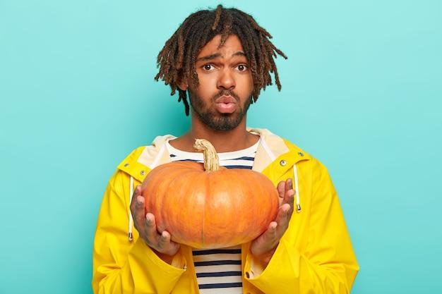 Niezadowolony hipster wygląda z niezadowoleniem, trzyma pomarańczową dynię, nosi żółty płaszcz przeciwdeszczowy, nosi dyni