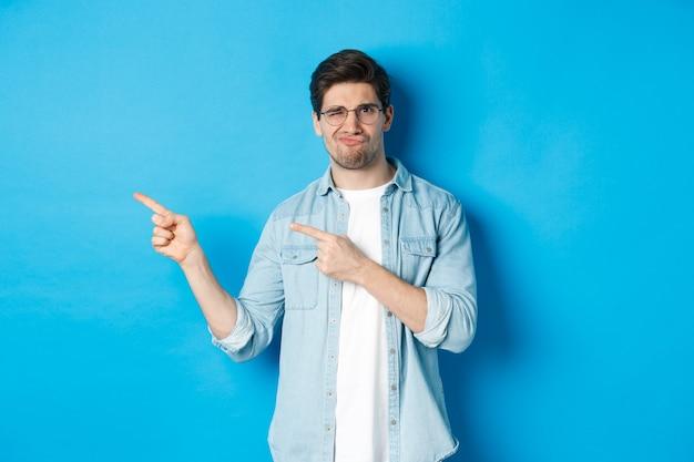 Niezadowolony i sceptyczny model w okularach, wskazujący palcami na coś złego, pokazujący okropną reklamę, stojący na niebieskim tle
