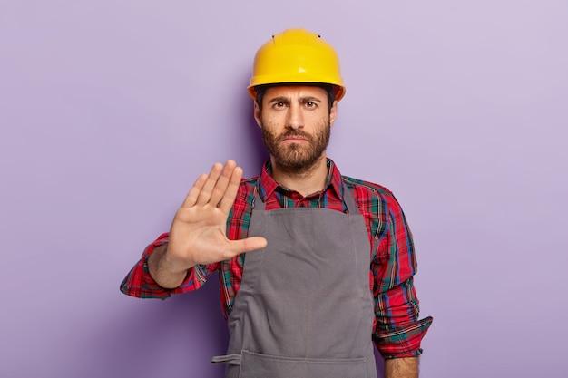 Niezadowolony inżynier wykonuje gest odrzucenia, mówi nie, trzyma dłoń wyciągniętą przed kamerą