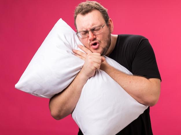 Niezadowolony kaszel w średnim wieku chory mężczyzna przytulił poduszkę