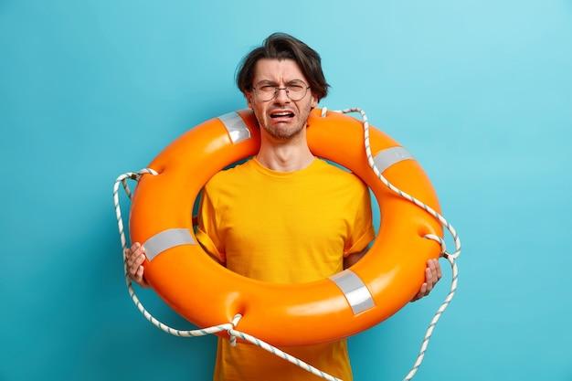 Niezadowolony kaukaski mężczyzna uczy się pływać w pozach z kołem ratunkowym, przygotowuje się do rejsu