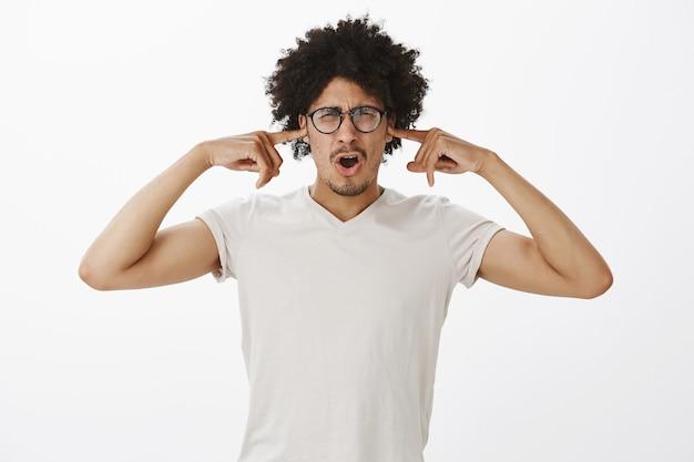 Niezadowolony kłócący się mężczyzna w okularach zatkał uszy od okropnego hałasu