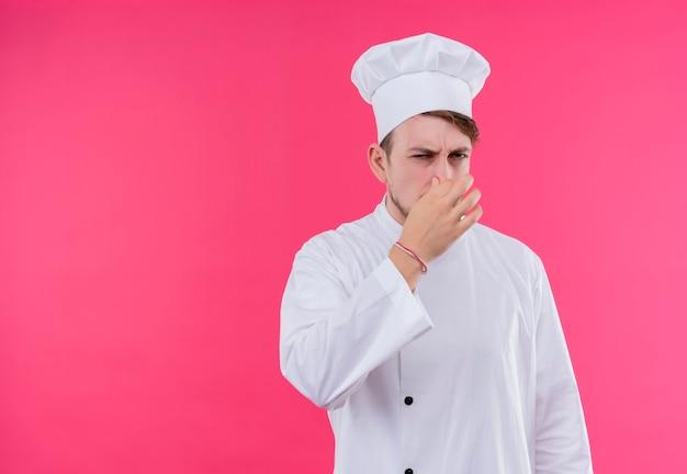 Niezadowolony kucharz patrzy na aparat i robi nieprzyjemny zapach stojąc na różowej ścianie