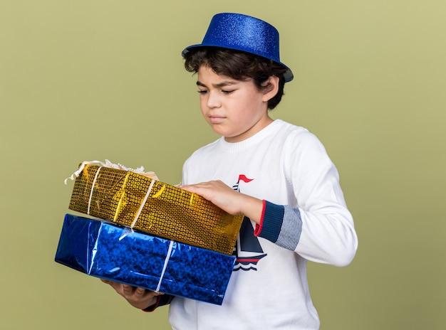 Niezadowolony mały chłopiec w niebieskiej imprezowej czapce, trzymający i patrzący na pudełka na prezenty na oliwkowozielonej ścianie