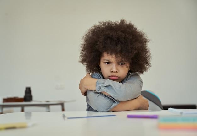 Niezadowolony mały uczeń z włosami w kolorze afro, wyglądający na rozzłoszczonego, marszczącego brwi podczas siedzenia z ramionami