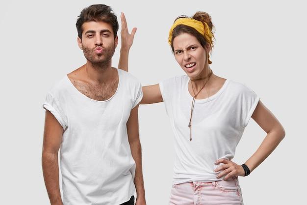 Niezadowolony małżonek trzyma rękę na talii, podnosi rękę i niezadowolony z zachowania męża, który flirtuje z inną kobietą i trzyma usta w pocałunku, ubrany w swobodny strój, stoi razem w domu
