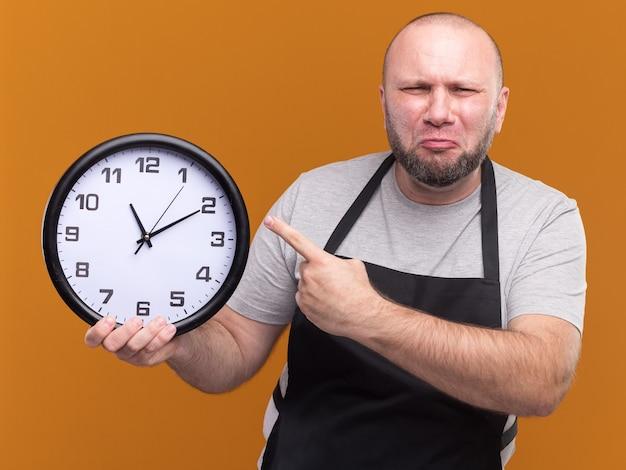 Niezadowolony męski fryzjer w średnim wieku w mundurze trzymającym i wskazujący na zegar ścienny odizolowany na pomarańczowej ścianie
