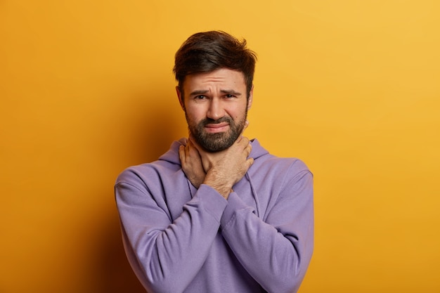 Niezadowolony mężczyzna dusi się bolesnym duszeniem w gardle, dotyka szyi, wygląda na niezadowolonego, ma ból gardła po przeziębieniu, ubrany niedbale, pozuje nad żółtą ścianą
