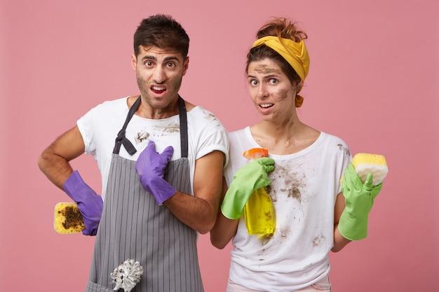 Niezadowolony mężczyzna i kobieta w brudnych ubraniach, trzymając gąbkę i spray do prania, którzy są nieporządni