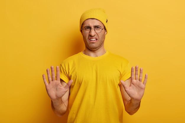 Niezadowolony mężczyzna odrzuca, odrzuca propozycję, dostaje złą ofertę, mówi nie z dwiema dłońmi wyciągniętymi w stronę aparatu, odmawia, nosi okrągłe okulary