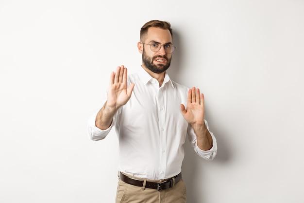 Niezadowolony mężczyzna odrzucający coś niepokojącego, pokazujący znak stop i odmawiający, kuli się z niechęci