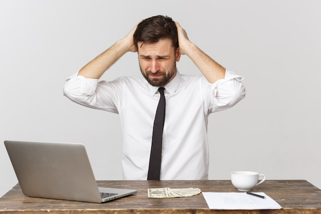 Niezadowolony mężczyzna pracujący w biurze, widok z przodu, na białym tle
