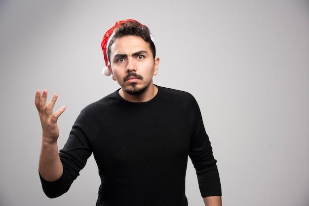 Niezadowolony mężczyzna w czerwonym kapeluszu świętego mikołaja na szarej ścianie.