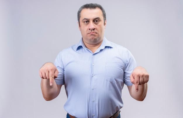 Niezadowolony mężczyzna w średnim wieku, ubrany w niebieską koszulę w pionowe paski, pokazujący palce wskazujące skierowane w dół podczas stania