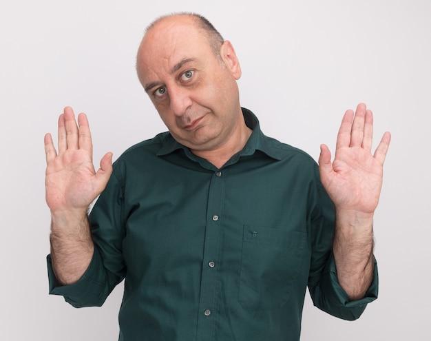 Niezadowolony mężczyzna w średnim wieku ubrany w zieloną koszulkę rozkładającą ręce na białej ścianie