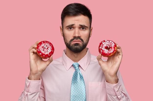 Niezadowolony mężczyzna z ciemnym zarostem, marszcząca brwi, trzyma dwa smaczne pączki w kształcie pierścienia, czuje się nieszczęśliwy, jak nie może jeść słodyczy