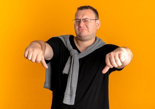 Niezadowolony mężczyzna z nadwagą w okularach, ubrany w czarną koszulkę, pokazujący kciuki w dół na pomarańczowo