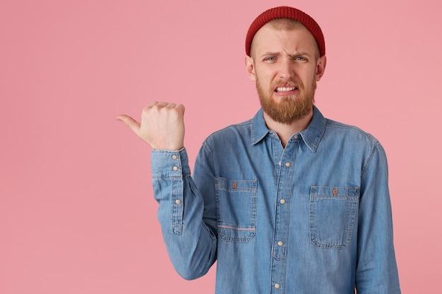 Niezadowolony mężczyzna z pomarszczoną twarzą, robi grymas obrzydzenia, jeden kącik ust jest podniesiony, wyraża niezadowolenie, irytację, wskazuje kciukiem w lewą stronę na miejsce na kopię, na różową ścianę