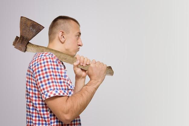 Niezadowolony mężczyzna z siekierą na ramieniu. białe tło