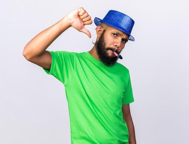 Niezadowolony młody afro-amerykanin w kapeluszu imprezowym dmuchający gwizdek pokazujący kciuk w dół