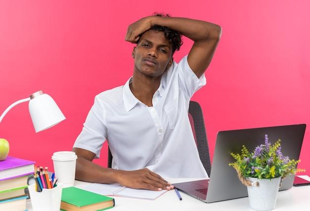 Niezadowolony młody afroamerykański uczeń siedzący przy biurku ze szkolnymi narzędziami, kładący dłoń na jego głowie