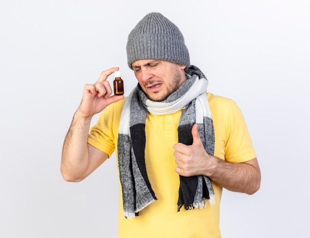 Niezadowolony młody blondyn chory w czapce zimowej i szaliku trzyma lekarstwo w szklanej butelce i kciuki do góry na białej ścianie