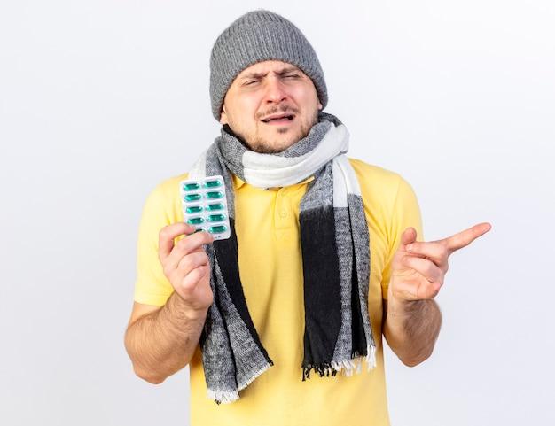 Niezadowolony młody blondyn chory w czapce zimowej i szaliku trzyma paczkę pigułek medycznych i wskazuje na bok na białym tle na białej ścianie