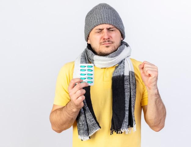 Niezadowolony młody blondyn chory w czapce zimowej i szaliku trzyma paczkę tabletek medycznych i trzyma pięść na białej ścianie