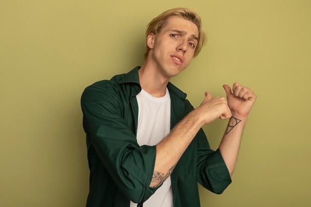 Niezadowolony młody blondyn w zielonej koszulce wskazuje na tył